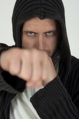 fist of man fighter with serious face punching in hood isolated on white background 版權商用圖片