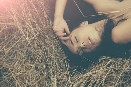 干し草で横になっている少女。目を閉じてとブルネットの髪を持つ女性。裸の肩を持つモデルします。夏の休暇の概念。レジャーと自然でリラック 写真素材