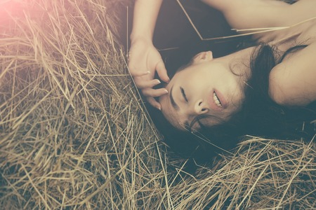 Girl lying in hay. Woman with closed eyes and brunette hair. Model with bare shoulders. Summer vacation concept. Leisure and relaxing on nature.