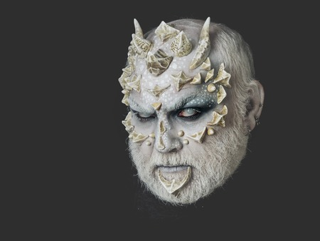 creepy alien: Man with dragon skin and grey beard. Monster with sharp thorns and warts on face. Horror and fantasy concept. Demon head on black background. Alien or reptilian makeup.