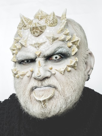 man or grimace monster with thorns on face with futuristic makeup as alien with beard and lens in eyes on white background