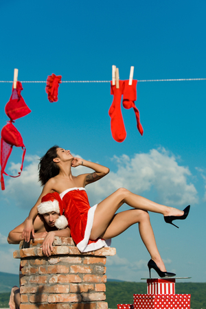 Christmas man and woman family. New year guy with muscular body on blue sky. Couple of man and girl on chimney. Xmas red present box. Stock Photo