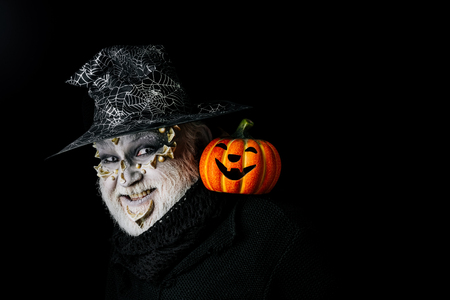 Sorcerer with dragon skin and grey beard on face. Magic and halloween concept. Man with orange pumpkin. Jack o lantern with spooky smile. Wizard in witch hat on black background, copy space