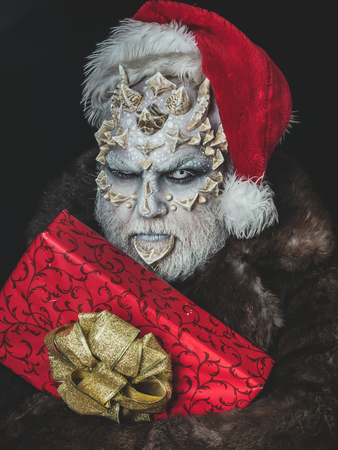 Man with red present box. Monster in santa hat and fur coat. Sorcerer face with white eyes and sharp thorns. Elf with dragon skin and beard. New year and christmas concept.