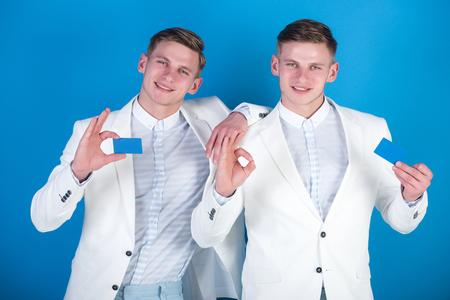 ビジネスマンの笑顔で白いジャケットのブルーの背景。男性 ok のジェスチャーで空白のカードを保持します。協力と連携。ビジネス コミュニケーシ