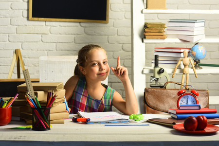 Girl has new idea while doing homework. Kid with colorful stationery on white wall background. Childhood and back to school concept. Pupil with books and school supplies. Zdjęcie Seryjne