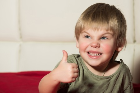 Small boy with thumb up. Kid with blonde hair. Childhood and success. Gesture and emotions. Child with angry face. Stok Fotoğraf - 85134392