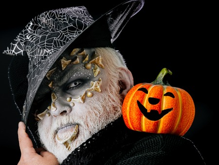 creepy alien: Sorcerer with dragon skin and grey beard on face. Wizard in witch hat on black background. Jack o lantern with spooky smile. Man with orange pumpkin. Magic and halloween concept.