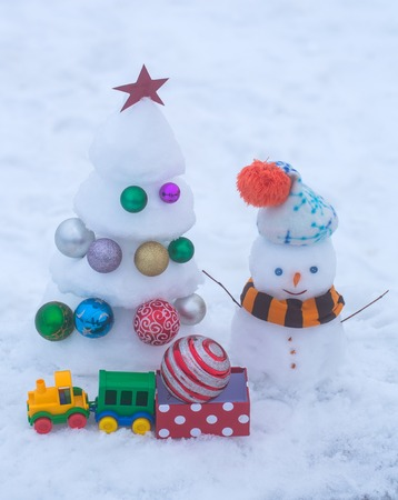 Snow sculptures on white background. Snowman with smiley face in hat and scarf. Christmas tree with decorations, toy train and present box. xmas and new year. Winter holidays concept. Stock Photo