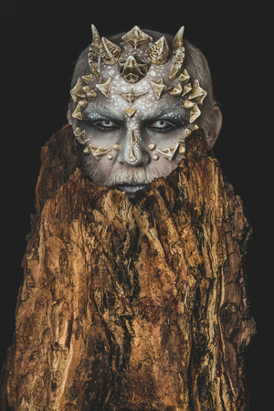 Monster with sharp thorns and warts. Goblin with horns on head. Tree spirit and fantasy concept. Druid behind old bark on black background. Man with dragon skin and bearded face. Stock Photo