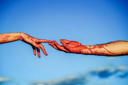 ゾンビの手が男性と女性の戦争の兵士の男と女の子または血の傷と青い空を背景には、皮膚上の赤い血の女性 写真素材 - 85139341
