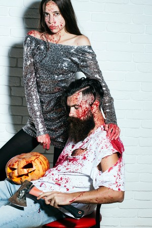 Halloween zombie couple of bearded man, long beard, brutal caucasian hipster with moustache hold pumpkin, axe and bloody woman with wounds and red blood in sequins dress on white brick wall background Stock Photo