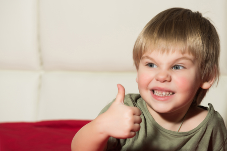 Small boy with thumb up. Gesture and emotions. Kid with blonde hair. Childhood and success. Child with angry face. Stock fotó