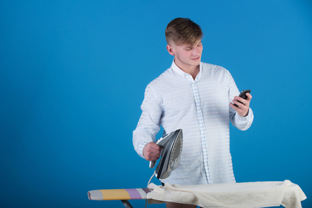 Guy talking on mobile phone on blue background. Macho wearing striped shirt. Housework and technology concept. Man ironing laundry on board. Model using iron.