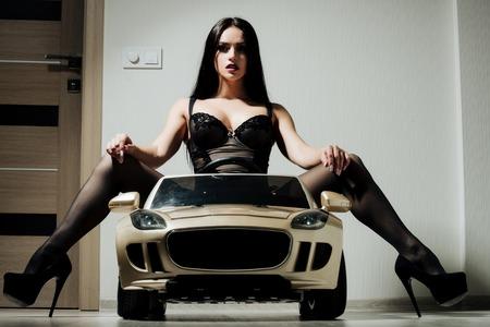 자동차 장난감에 소녀입니다. 에스코트 및 성행위. 드라이버 소녀 자동차에 앉아. 아름다움과 패션. 검은 란제리와 신발 여자입니다.