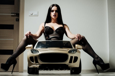 Girl in car toy. escort and services. Driver girl sit in car. Beauty and fashion. Woman in black lingerie and shoes.