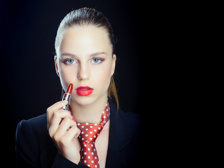 Woman with red lips and tie. Girl applying lipstick. Model with perfect make up on black background. Cosmetics and makeup products. Beauty and fashion concept, copy space