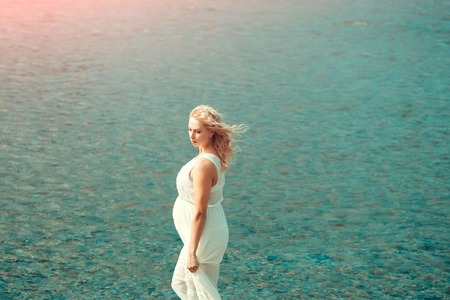 Pregnancy and fertility. Motherhood and maternity concept. Pregnant woman in white dress walking on sea beach on sunny day on blue water. Mother with big belly expecting baby.