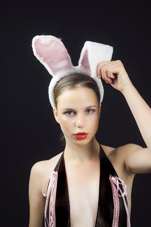 Playboy girl posing on black background. Woman with red lips wearing rabbit ears. Sexy bunny model. Easter holiday concept. Stock Photo