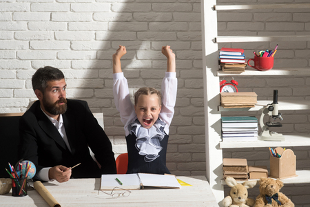Daughter and father in classroom on white brick background. Education and family relationship concept. Schoolgirl and dad with cheerful and surprised faces. Man and girl by desk with school supplies