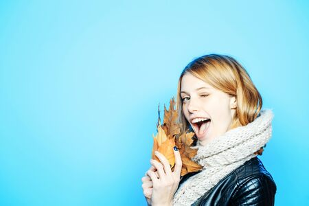 Season and autumn holiday. happy model with stylish hair in scarf. Girl with orange leaves on blue background. Beauty and fashion. Woman with autumn leaves in leather jacket, copy space Stock Photo