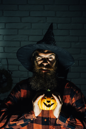 Halloween hipster winking in witch hat and plaid shirt. Mystery and horror concept. Holiday celebration symbols on brick wall. Jack o lantern. Man with pumpkin in darkness.
