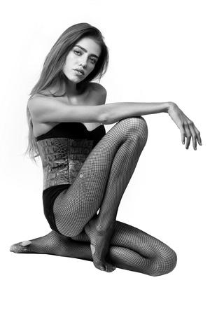 schoonheid of meisje met lang haar en benen in visnetlegging en modieus leren bodysuit, zwart en wit