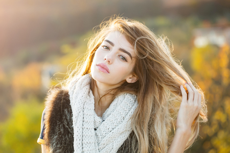 Fashion model with pretty face. Girl on autumn natural background. Season and fall holiday. Beauty and fashion. Woman with long hair and natural makeup.