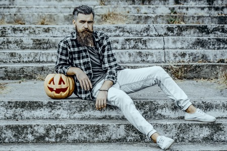 Halloween man and pumpkin outdoors. Bearded hipster sitting on stony stairs. Halloween jack o lantern with carved face. Holiday celebration concept