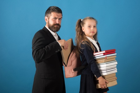 Classroom and alternative education concept. Bearded man and girl in school uniform. Teacher and schoolgirl with grumpy faces on blue background. Kid holds books stack and tutor puts book into bag