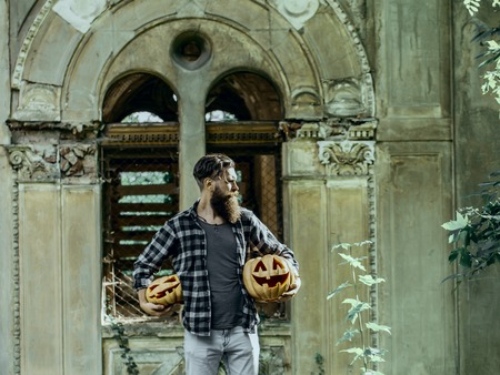 Halloween man with pumpkins on abandoned building. Bearded hipster standing outdoors. Halloween jack o lanterns with carved faces. Holiday celebration concept