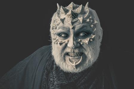맹인 눈으로 화가 난 남자. 치아 검정색 배경에 baring 악마입니다. 가시와 뿔이있는 괴물. 드래곤 피부와 회색 수염을 가진 사악한 얼굴. 공포와 판타지