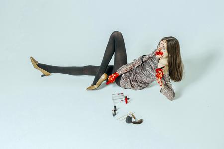 Halloween-vrouw die op vloer ligt die op wit wordt geïsoleerd. Meisje met bloedig gezicht en lang donkerbruin haar. Mannequin in grijze feestjurk. Dame met lippenstift en make-upkit. Halloween make-up concept. Stockfoto