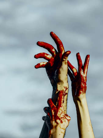 Halloween zombie hands on grey sky background. Bloody hands with red blood stretching up. Maniac or murderer concept. Halloween holiday celebration Stock Photo
