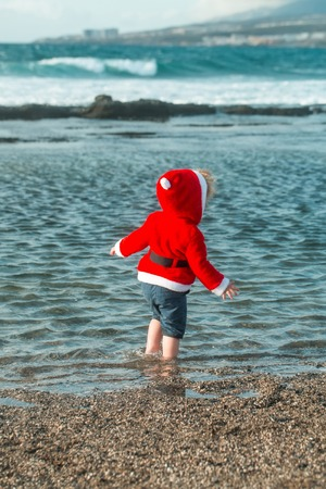 Cute baby boy in red santa coat with hood and wet shorts walks barefoot in blue sea water on pebble beach on sunny summer day on natural background Stock Photo