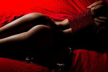 Sexy vrouw die op rood bed legt. Schoonheid en mode. Billen van meisje in lingerie. Vrouw in erotische ondergoed broek.