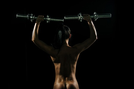 Activity and energy. Sexy girl with metallic dumbbell or barbell. Coach and health. Sport and weightlifting. Woman with naked body at workout.