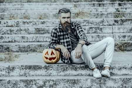 Halloween hipster sitting on stony stairs. Bearded man and pumpkin outdoors. Halloween jack o lantern with carved face. Holiday celebration concept Stock Photo
