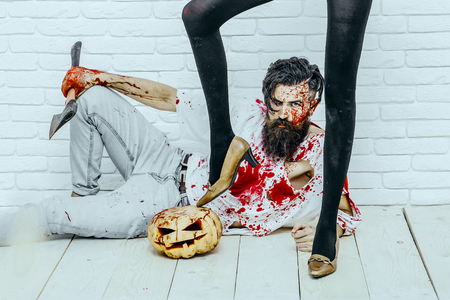 Halloween female legs black pantyhose and shoes standing on pumpkin. Hipster sitting with pumpkin and axe on wooden floor. Bearded man with red blood splatters. Halloween holiday celebration concept
