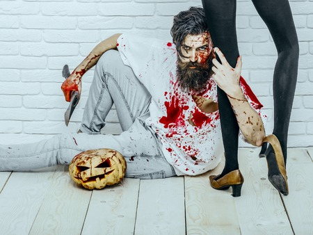 Halloween man holding female legs in black pantyhose. Brutal hipster sitting with pumpkin and axe on wooden floor. Vampire with red blood splatters. Halloween holiday celebration concept Stock Photo