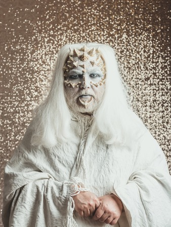 Wizard with long silver hair. Demon in white cloth on golden bokeh background. Monster with thorns and warts on face. Mystery and fantasy concept. Man with grey beard and dragon skin.