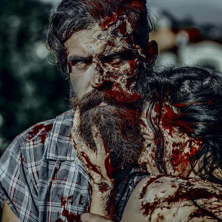 Halloween vampire man with beard and wounds. Woman with red blood and brunette hair. Holiday celebration concept. War soldier and girl with bloody skin. Zombie couple hugging on natural background. 版權商用圖片