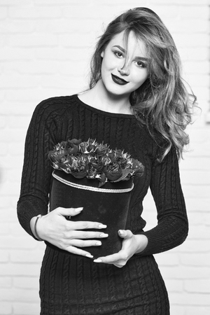 woman or girl with long blond hair has lipstick and dress holds rose flowers bouquet in box, black and white