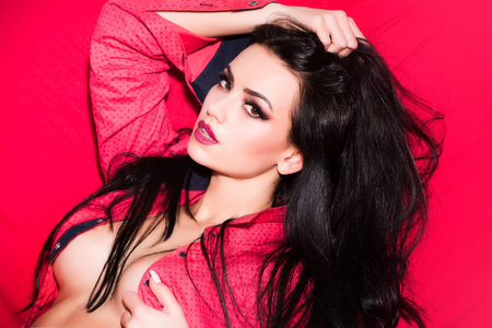 長いブルネットの髪や顔にファッショナブルな化粧とファッション モデルは赤の背景に裸の体をします。