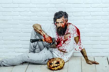 Halloween man sitting with pumpkin and axe on wooden floor. Maniac and bloody jack o lantern. Halloween holiday concept. Psychopath bleeding in torn tshirt. Bearded hipster with red blood splatters.
