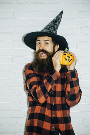 Halloween trick or treat. Happy man with pumpkin on white brick wall. Jack o lantern. Hipster with beard in wizard hat. Holiday celebration concept. Stock Photo