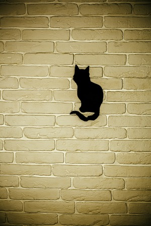 Halloween black cat silhouette paper cutout on beige brick wall. Mystery and superstition concept. Holiday celebration symbol, copy space