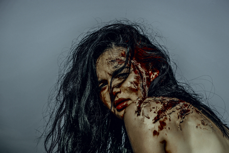 Halloween woman with red blood on naked shoulders. Zombie posing on blue sky. Vampire with long brunette hair. Holiday celebration concept. Girl with bloody wounds on skin.