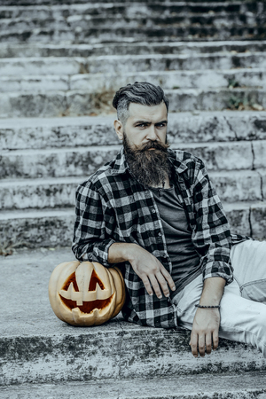 Halloween jack o lantern with carved face. Bearded hipster sitting on stony stairs. Halloween man and pumpkin outdoors. Holiday celebration concept