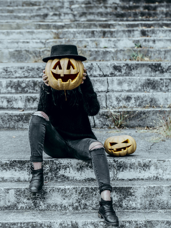 Halloween holiday celebration concept. Fashion model in black hat and clothes. Girl with pumpkin head. Halloween jack o lantern symbols. Woman sitting on stony stairs.